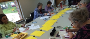 A group of writers in a poetry session. About 7 people are in the image, gathered around a long table. On the table are colored paper, chocolate, cookies, and postcards.