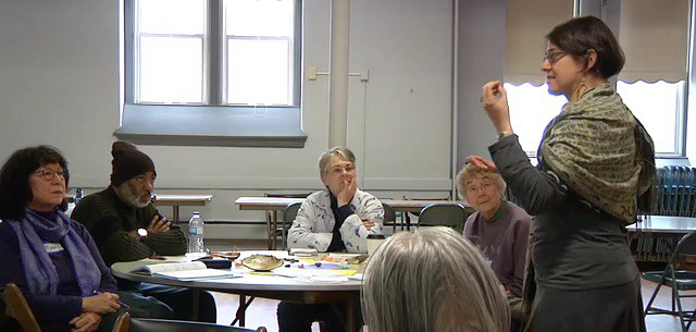 Naomi leading a poetry session at Saint Anthony Park Area Seniors.She is standing on the right; a group of participants is seated in the left of the image.